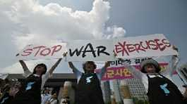 "Anti-war activists hold placards reading ""Stop War Exercises"" during a rally"
