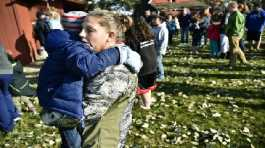 Marnie Wedgwood hugs her son evacuated from the Rossiter Elementary School in Helena, Mont.