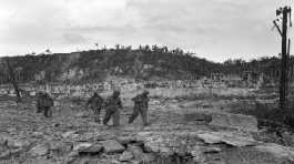 U.S. soldiers walk by a bombed out cemetery in Agana, Guam