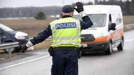 A police officer stops a vehicle for a document check at a traffic control post