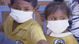 Masked children wait to get vaccinated